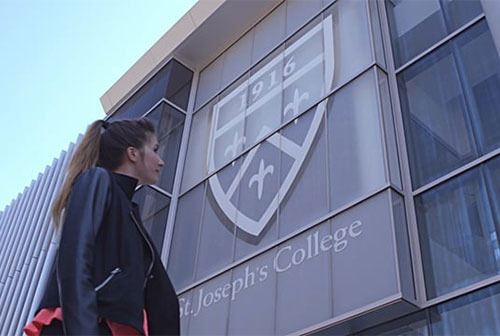 girl looking at school logo on new building